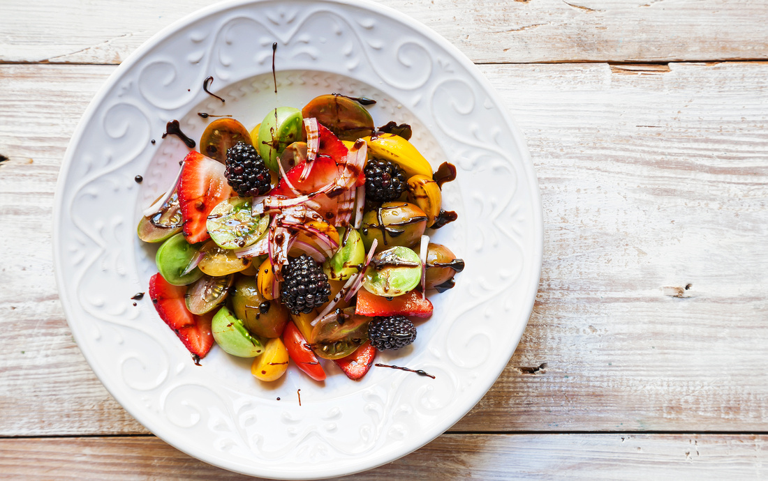 bowl of fruit salad with blackberries, strawberries, heirloom tomatoes and a balsamic reduction