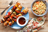 Chicken kebobs on skeweres with barbecue sauce and orzo pasta salad
