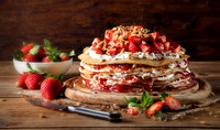 a stack of crepes with cream cheese and strawaberries in between layers