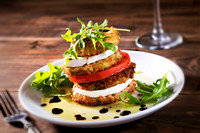 stacked eggplant with tomatoes mozzarella and arugula