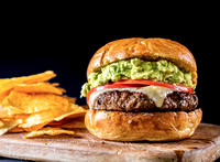A juicy cheeseburger topped with guacamole and tomatoes