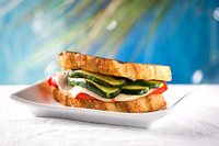Picture of a sandwich containing grilled zucchini, roasted peppers and provolone